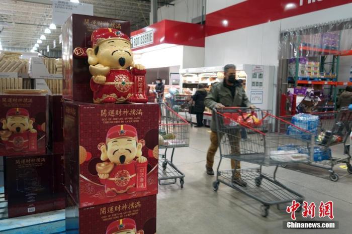 当地时间12月31日,顾客在加拿大多伦多一间大型仓储购物店内购物,迎接即将到来的2021年。图为店内售卖的财神爷造型存钱罐。<a target='_blank' href='http://www.chinanews.com/'>中新社</a>记者 余瑞冬 摄
