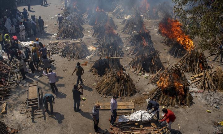 周六,在印度新德里的一处因大规模火化而改建的现场中,多处COVID-19受害者的葬礼堆被燃烧。 当印度政府连续第三天报告了超过34.6万例感染的全球每日新记录时,印度当局正争先恐后地向医院提供医用氧气。 照片:AP